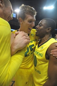 E.J. Singler (center) celebrates with Jonathan Loyd (right) after the Ducks' 70-66 victory over the Arizona Wildcats. (Photo by Rockne Andrew Roll)