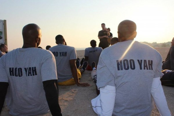 "SEAL Team Physical Training founder John McGuire talks to the Toledo men's basketball team, which has just earned shirts with the Navy's ""Hoo yah"" slogan on their back. (Courtesy of SEAL Team Physical Training)"