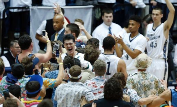 George Washington forward Yuta Watanabe, left of center, smiles as he celebrates with fans that stormed the court after an NCAA college basketball game against Virginia, Monday, Nov. 16, 2015, in Washington. George Washington won 73-68. (AP Photo/Alex Brandon)